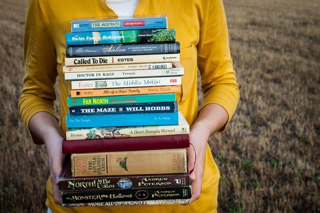Teen holding a stack of books